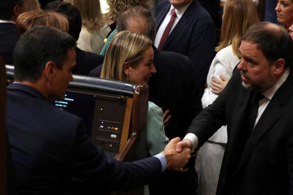 El presidente del Gobierno en funciones, Pedro Sánchez (i), saluda al diputado electo en prisión preventiva de ERC Oriol Junqueras, durante la sesión constitutiva de las nuevas Cortes Generales que se celebra este martes en el Congreso de los diputados de Madrid.