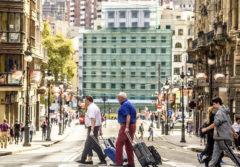Varios turistas caminan con sus maletas por el centro de Bilbao con el Arenal al fondo.