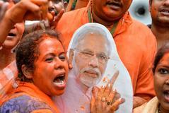 Una simpatizante del partido Bharatiya Janata abraza una figura de Narendra Modi en Siliguri (India).