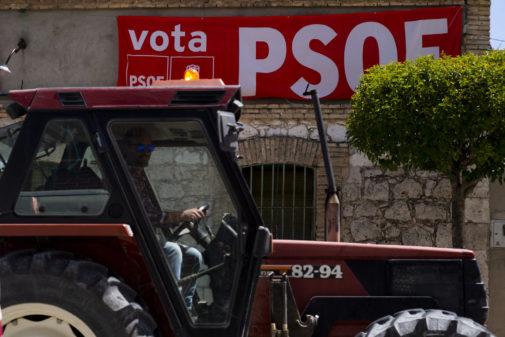 Un tractor pasa ante un cartel electoral del PSOE, esta semana en Quintanilla de Onésimo (Valladolid)