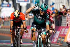 Winner Team Bora rider Italy's Cesare Benedetti (R) reacts as he crosses the finish line ahead of second-placed Team Bahrain rider Italy's Damiano Caruso (L) and third-placed Team Ineos rider Ireland's Eddie Dunbar (R) at the end of stage twelve of the 102nd <HIT>Giro</HIT> d'Italia - Tour of Italy - cycle race, 158kms from Cuneo to Pinerolo on May 23, 2019. (Photo by Luk BENIES / AFP)