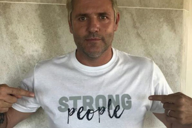 """Cañizares muestra una camiseta que reza """"gente fuerte""""."""
