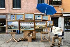 Un hombre, que podría tratarse de Banksy, está sentado al lado del montaje de pinturas 'Venice in oil'