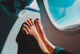 Pies descalzos contra el asiento de delante en un avión.
