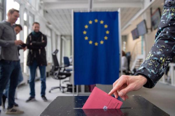 Una votante deposita en una urna su voto por correo para las elecciones al Parlamento Europeo