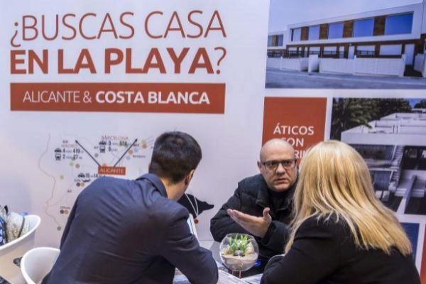 Un comercial de una promotora informa en el SIMA a unos clientes sobre la oferta disponible en la Costa Blanca.