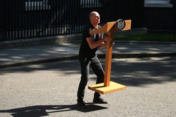 Un trabajador coloca, ayer, un atril frente al número 10 de Downing Street, en Londres, cuartel general de la jefatura del Gobierno británico.