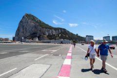 Unos turistas pasean por la pista del aeropuerto de Gibraltar.