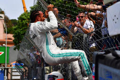 First placed Mercedes' British driver <HIT>Lewis</HIT> <HIT>Hamilton</HIT> (L) bends over after jumping at a fence to greet fans as he celebrates winning the pole position after the qualifying session at the Monaco street circuit on May 25, 2019 in Monaco, ahead of the Monaco Formula 1 Grand Prix. (Photo by Andrej ISAKOVIC / AFP)