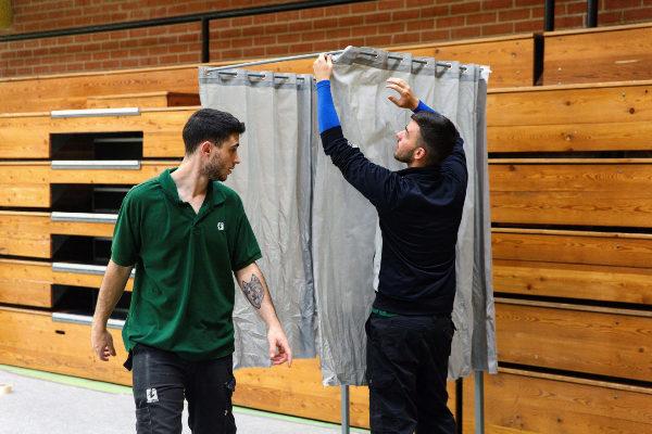 Unos trabajadores preparan un colegio electoral.