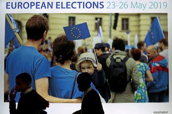 Ciudadanos pasan junto a un anuncio de los comicios, en Bruselas.