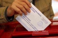 Un hombre introduce su voto para las elecciones europeas, en Riga.