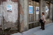 Una mujer observa un cartel electoral en la localidad coruñesa de Melide.