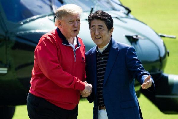 El presidente de EEUU, Donald Trump, saluda al Primer Ministro japonés, Shinzo Abe, antes de jugar al golf.