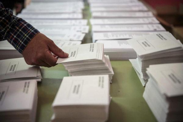 Un hombre coge un sobre en un colegio electoral de Valencia.