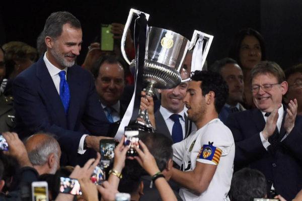 El capitán del Valencia recibe la Copa del Rey de mano del Rey Felipe VI.