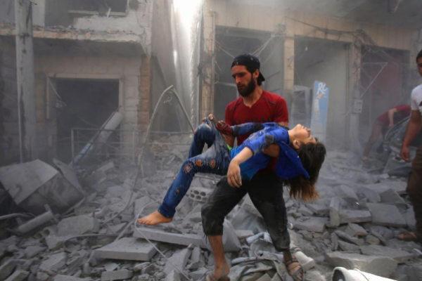 Un hombre saca una víctima de un bombardeo en la ciudad siria de Maaret Al-Noman, este domingo.