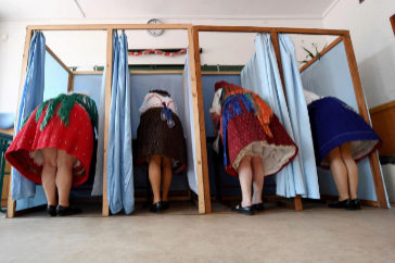 <HIT>TOPSHOT</HIT> - Women dressed in traditional Hungarian outfits vote for the European elections at a polling station in a school in Veresegyhaz, near Budapest, on May 26, 2019. (Photo by ATTILA KISBENEDEK / AFP)