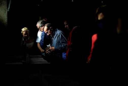 Un grupo de ciudadanos coge papeletas en el colegio San Agustín en...