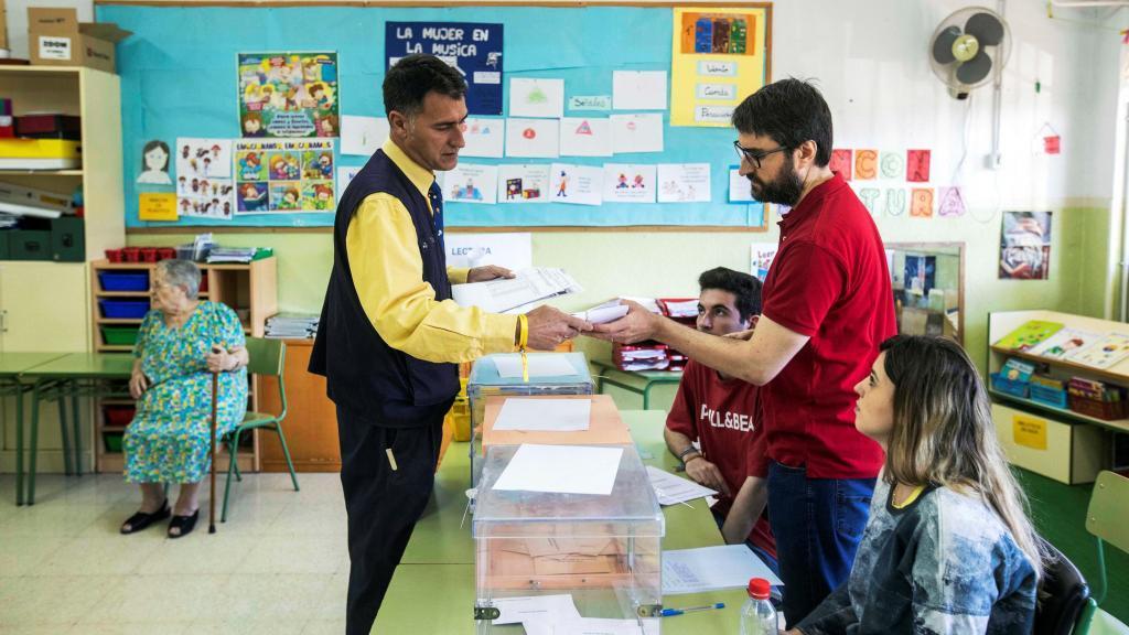 Un cartero entrega el voto por correo en una mesa electoral del Colegio San Andrés en Murcia
