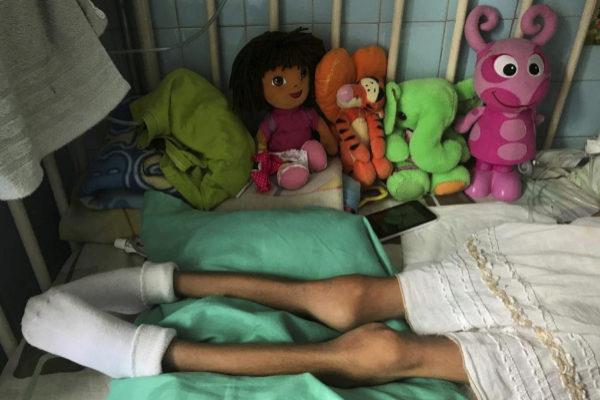 """A girl lays on a bed at the """"J.M. de los Rios"""" Children Hospital in..."""