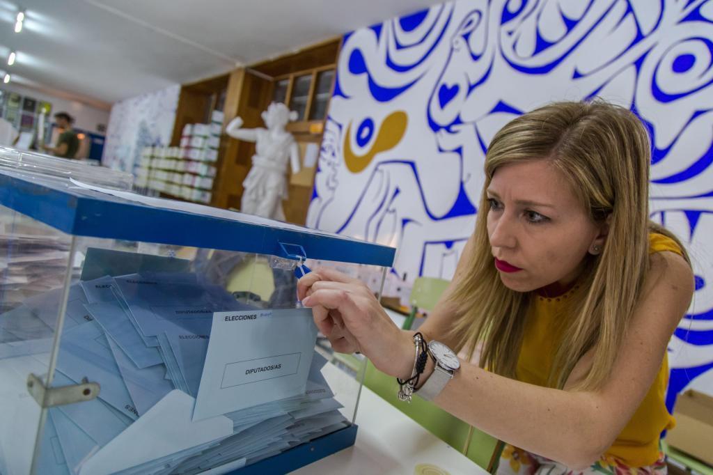 La Presidenta de una de las mesas electorales en Murcia procede a la apertura de la urna para el recuento de papeletas tras la jornada electoral.