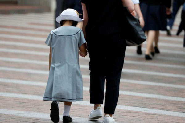 A <HIT>student</HIT> accompanied by her mother enters at a school whose students were victims by a stabbing in Kawasaki
