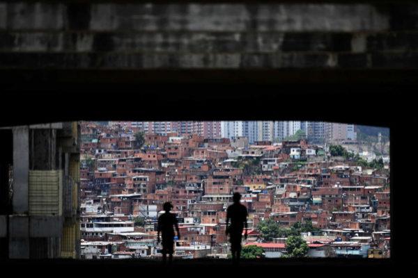 Dos personas caminan con la ciudad de Caracas al fondo.