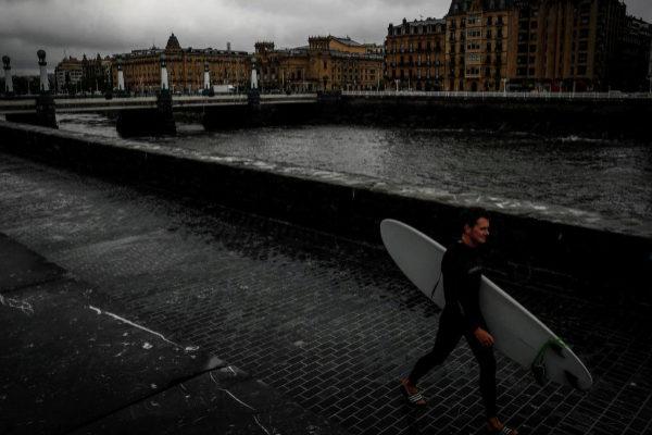 Un surfista camina con su tabla junto al río Urumea en el centro de San Sebastián.