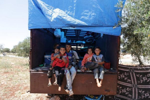 <HIT>Children</HIT> sit on the back of a truck in an olive grove at the town of Atmeh