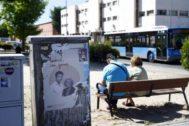 Una pareja en un banco frente al cartel de campaña de Más Madrid.
