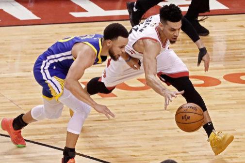 El jugador de los Toronto Raptors, Danny Green (d) va por un balón suelto contra el jugador de Golden State Warriors, Stephen Curry (i), durante el primer partido de la final de la NBA, disputado este jueves en el Scotiabank Arena de Toronto (Canadá).