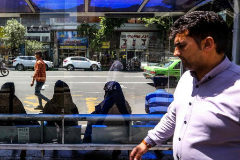 Un hombre camina por delante de una para de bus conde esperan varias mujeres en Teherán.