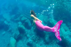 Una joven nada con cola de sirena.