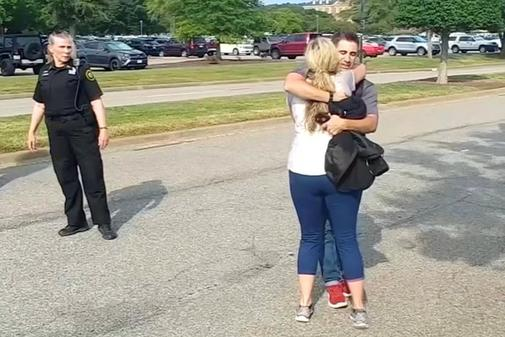 People embrace after being evacuated from a building by police in this...