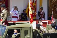 Felipe VI saluda al paso de un vehículo militar en el desfile de Sevilla.