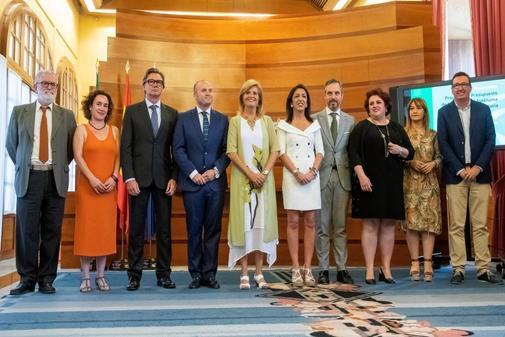 El consejero de Hacienda, Juan Bravo (4d), y la presidenta del Parlamento andaluz, Marta Bosquet (5d), posando en el Parlamento con los representantes de los grupos parlamentarios tras serle entregado el proyecto de ley de presupuestos.
