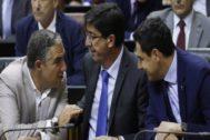 Elías Bendodo conversa con Juan Marín y Juan Manuel Moreno, durante el pleno este miércoles.