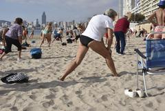 Un grupo de jubilados practica gimnasia en la playa de Poniente de Benidorm