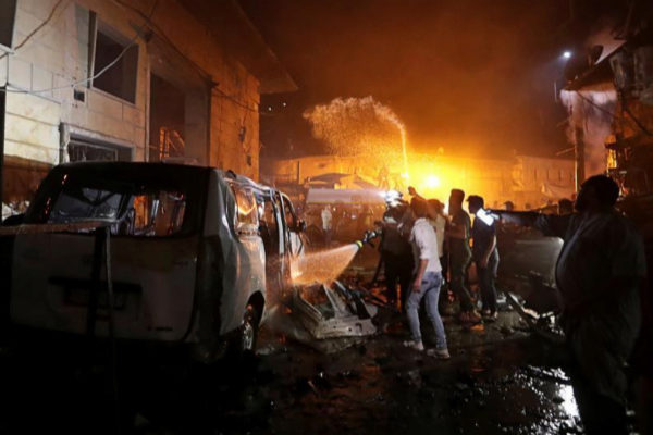 People try to extinguish a fire at the site of a car bomb blast in <HIT>Azaz</HIT>