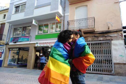 Dos personas se besan envueltos con la bandera LGTBI.