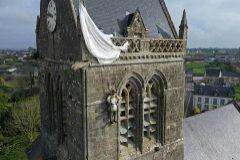Un maniquí en homenaje al paracaidista John Steel cuelga de la torre de una iglesia en Sainte-Mére- Eglise.