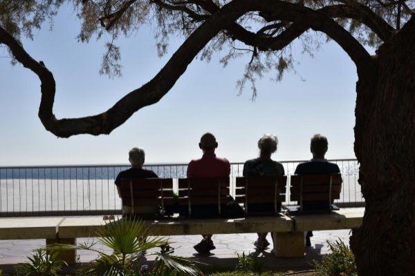 Un grupo de mayores contempla el mar sentados en uno de los bancos del paseo de Poniente de Benidorm, en una imagen de archivo.