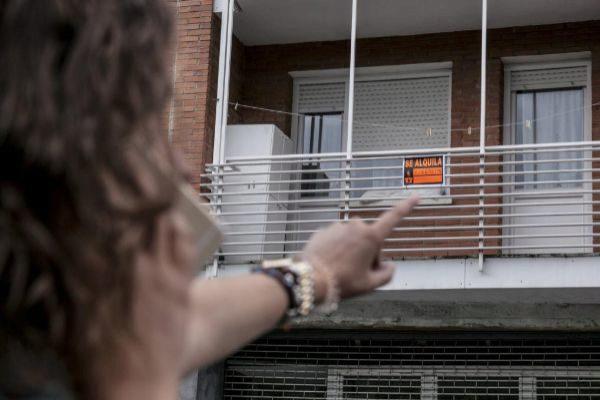 Una mujer pasa por delante de un edificio con viviendas en alquiler.