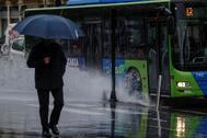 Un hombre pasea bajo la lluvia en San Sebastián
