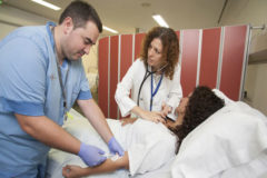 Una médico y un enfermero atienden a un paciente.