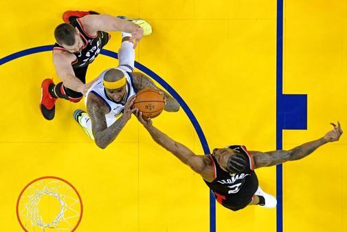 DeMarcus Cousins (0), de los Golden State Warriors, tira la pelota contra el delantero de Toronto Raptors Kawhi Leonard (2) en el juego tres de las finales de la NBA 2019 en Oracle Arena.