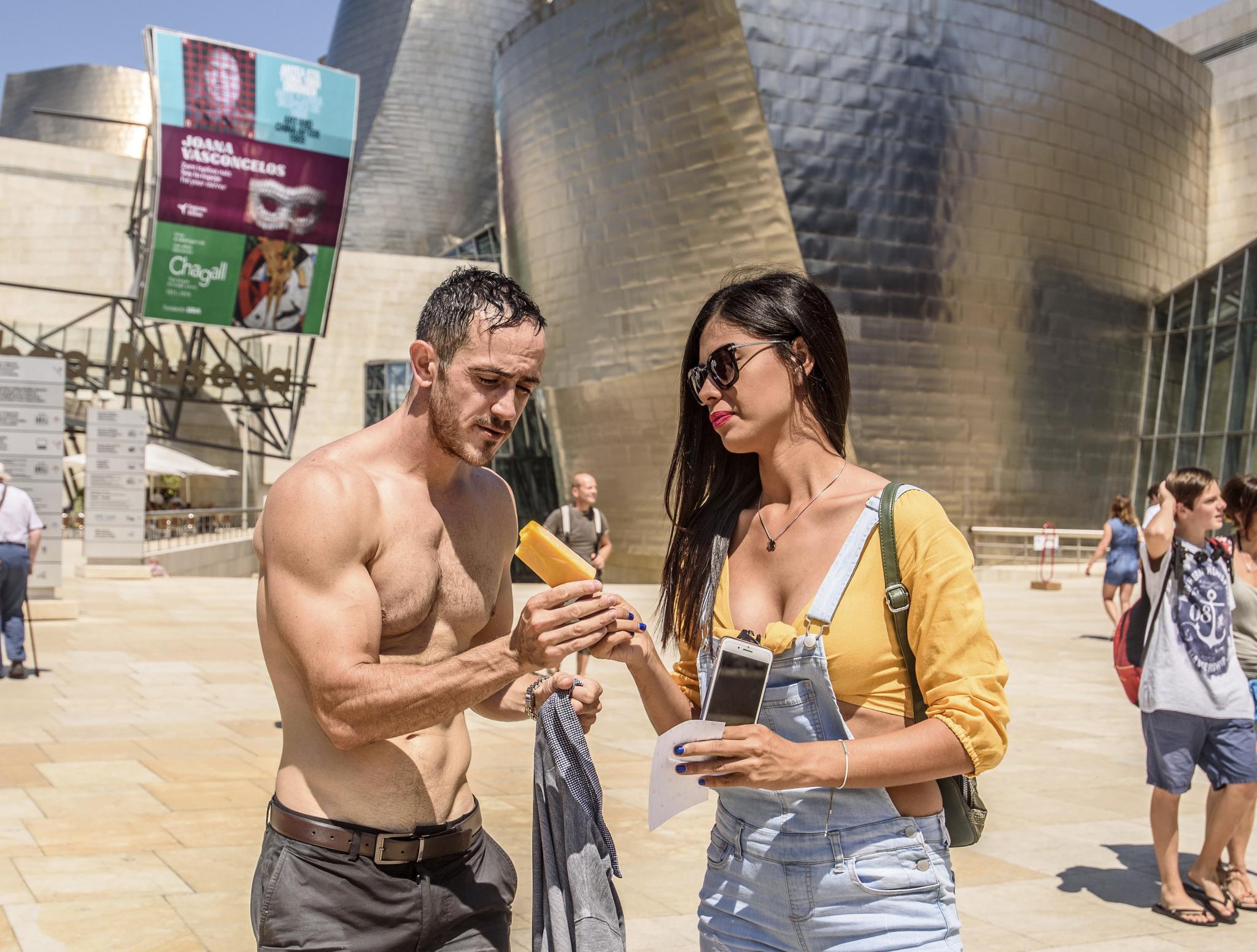 Una pareja se refresca con un helado junto a la explanada del Guggenheim en Bilbao.