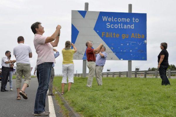 Un grupo de turistas toma fotos en la frontera entre Inglaterra y Escocia.