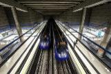Dos convoyes de metro pasando por una estación.
